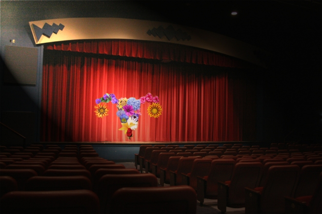A stage with the Bloomin' Uterus logo centered on it in a spotlight