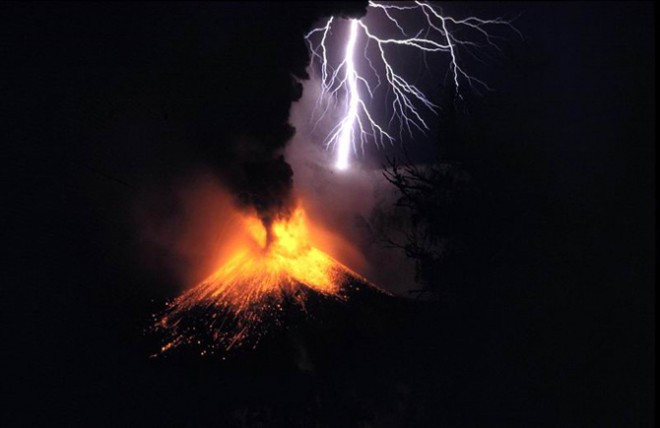 erupting volcano with lightning in the background