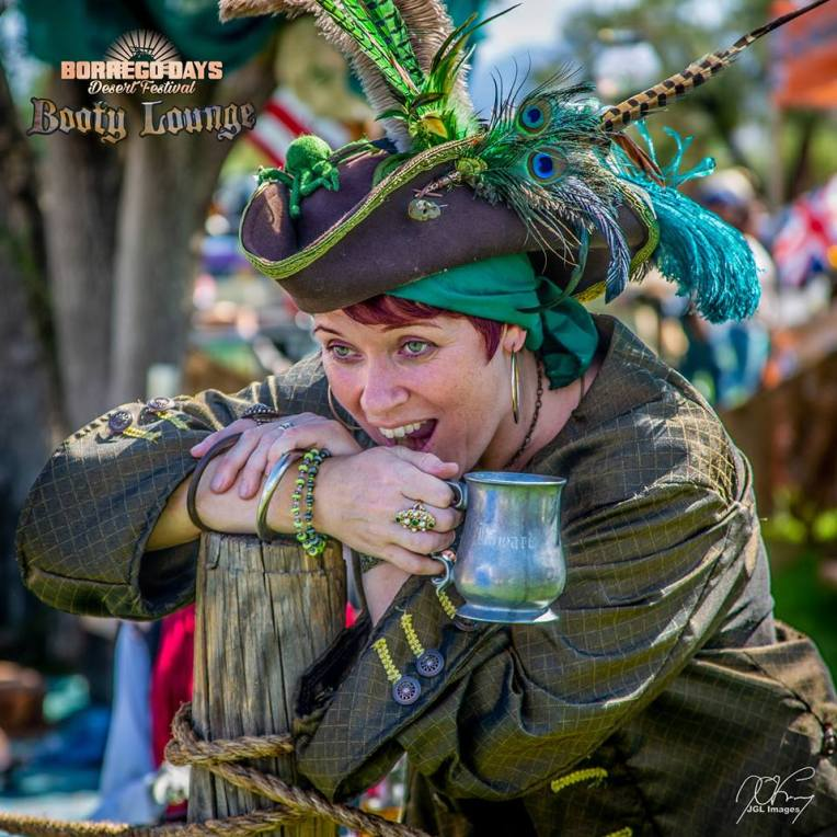 A red-headed pirate laughing and holding her tankard of ale