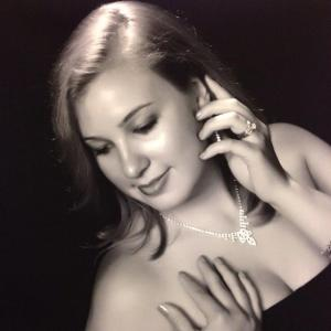 black and white photo of a glamourous woman in a gown and wearing diamond jewelry