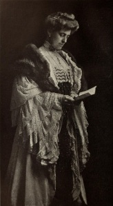 Edith Wharton in Victorian-era gown and reading a book