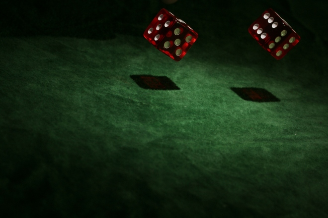 two red dice rolling on a green felt table