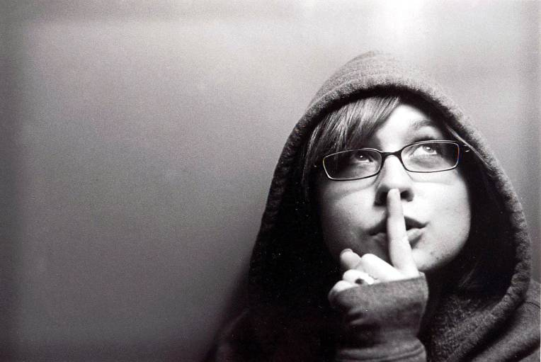 Woman holding her index finger to her lips to shhh someone