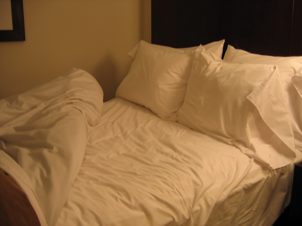 A bed with the blankets drawn back revealing the sheets and four pillows