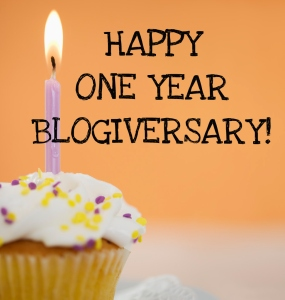 cupcake with a lit candle and the text happy one year blogiversary