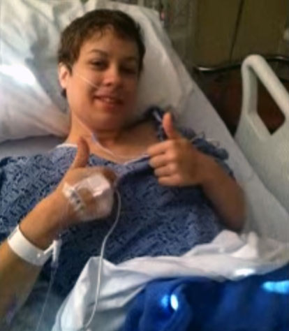 A young woman in a hospital bed giving two thumbs up