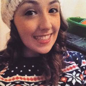 woman with curly brown hair wearing a sweater and beanie