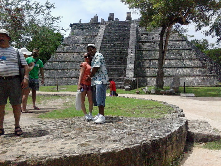 husband and wife hugging in front of mayan pyramid