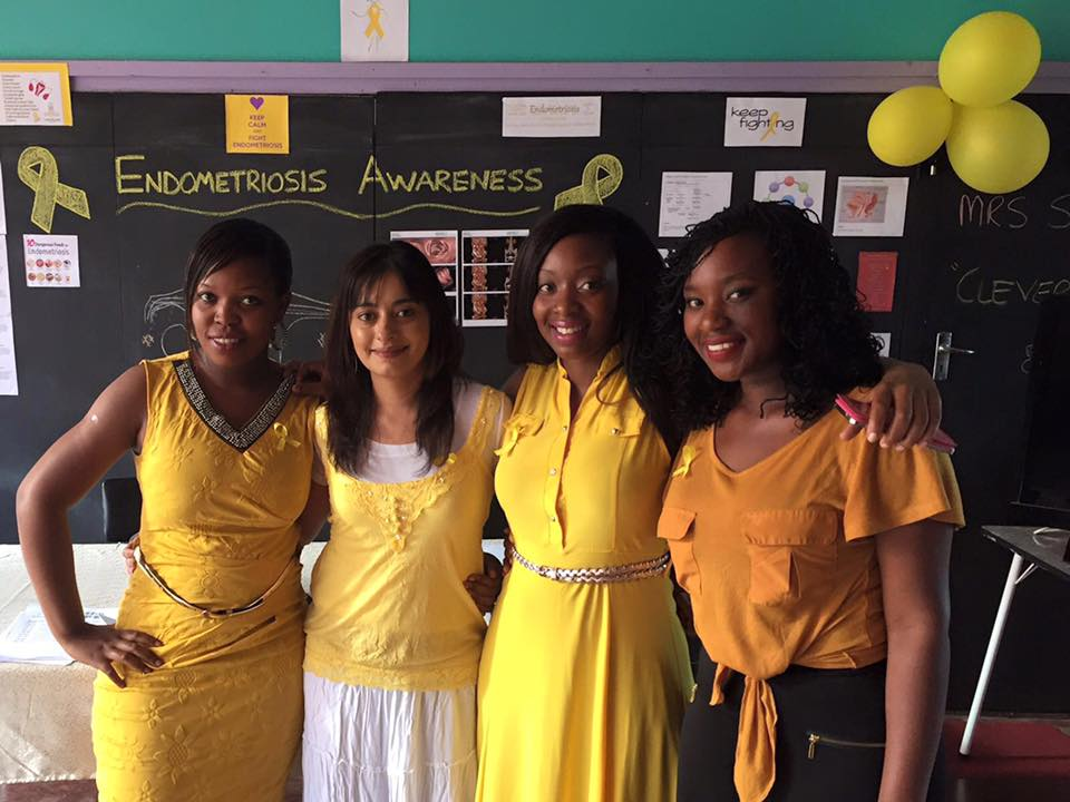 Four women dressed in yellow standing next to each other