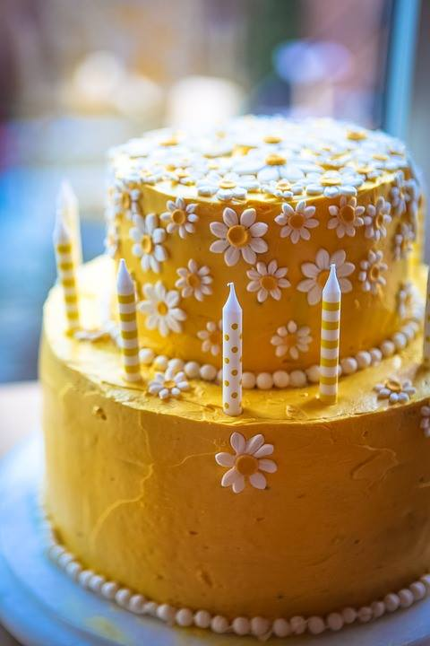 yellow birthday cake decorated with candles and white daisies