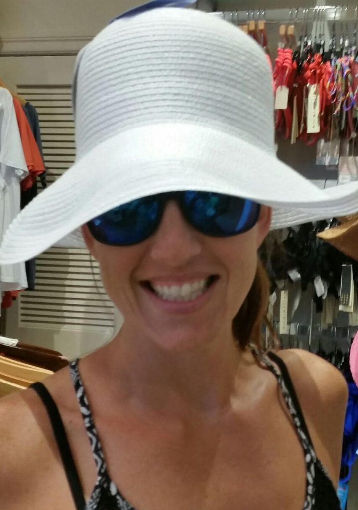 Smiling Caucasian woman in a big floppy white hat and sunglasses