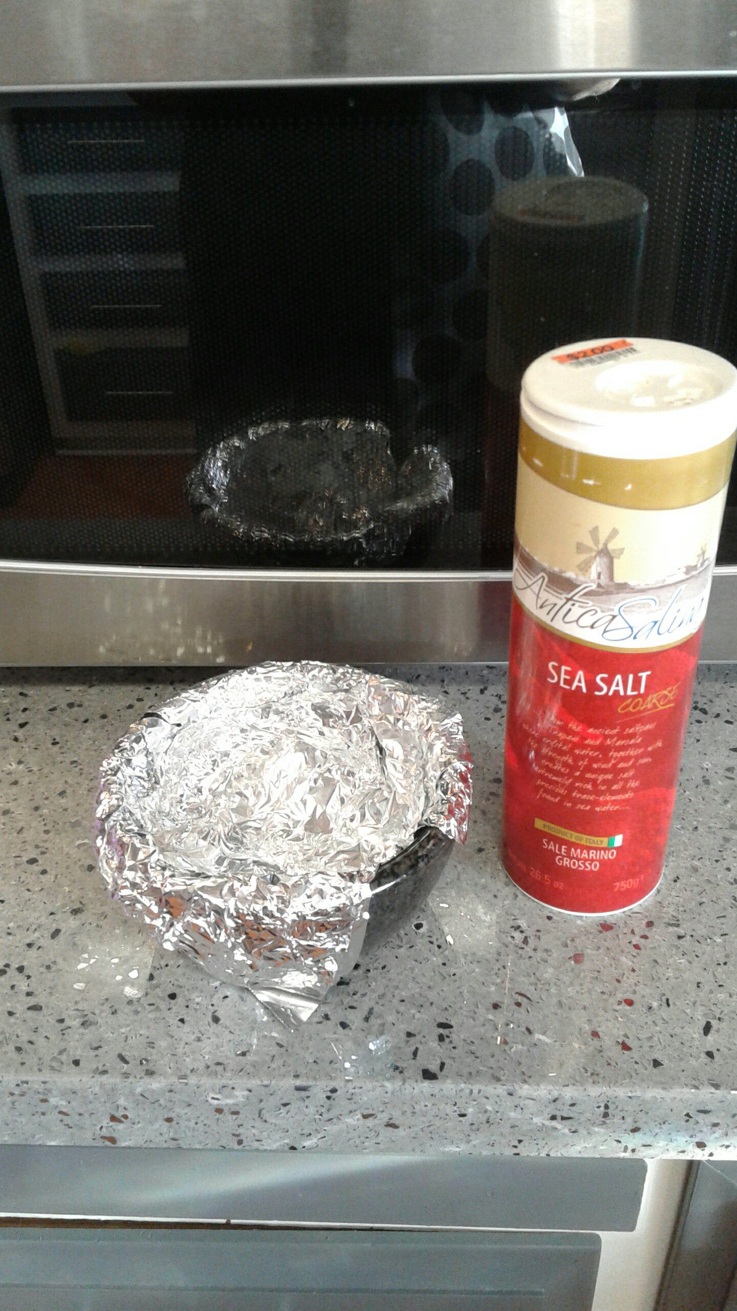 a bowl lined in aluminum foil next to a canister of sea salt