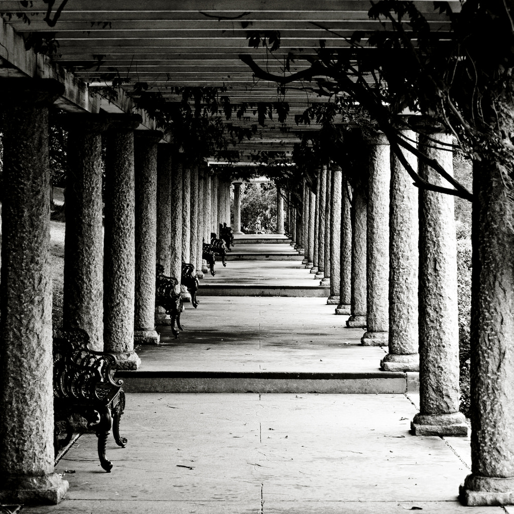 A path lined with marble pillars and benches