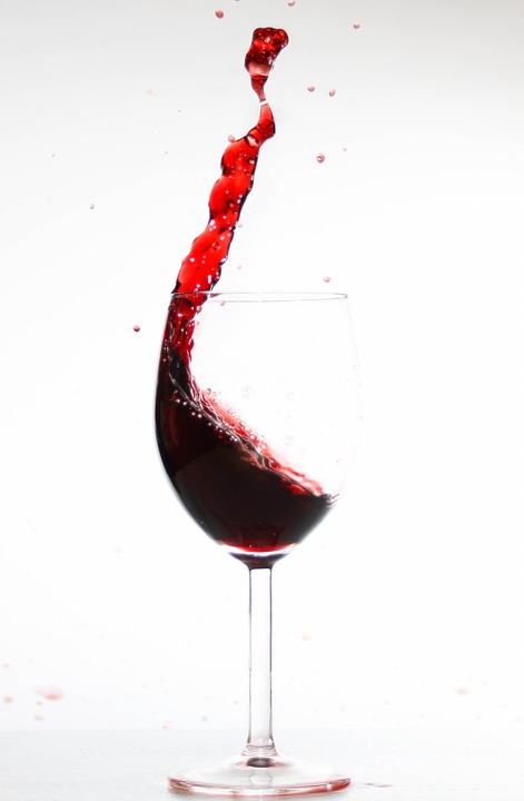 A spilling glass of red wine