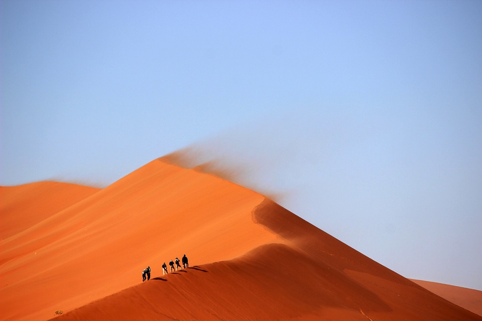 People walking on a sand dune in a vast desert