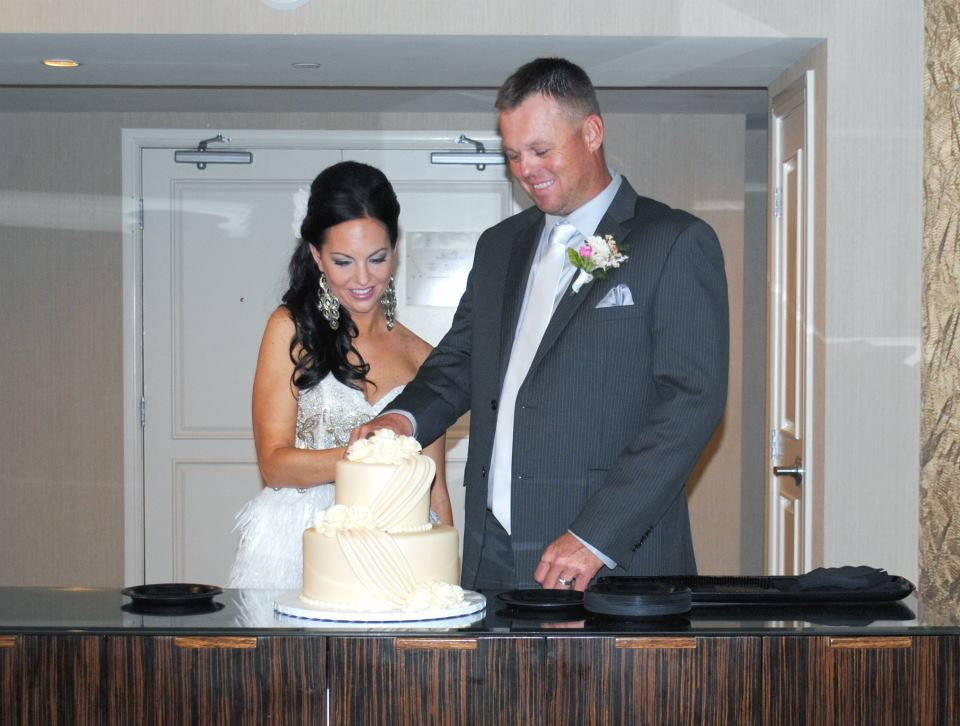 man and woman cutting a wedding cake