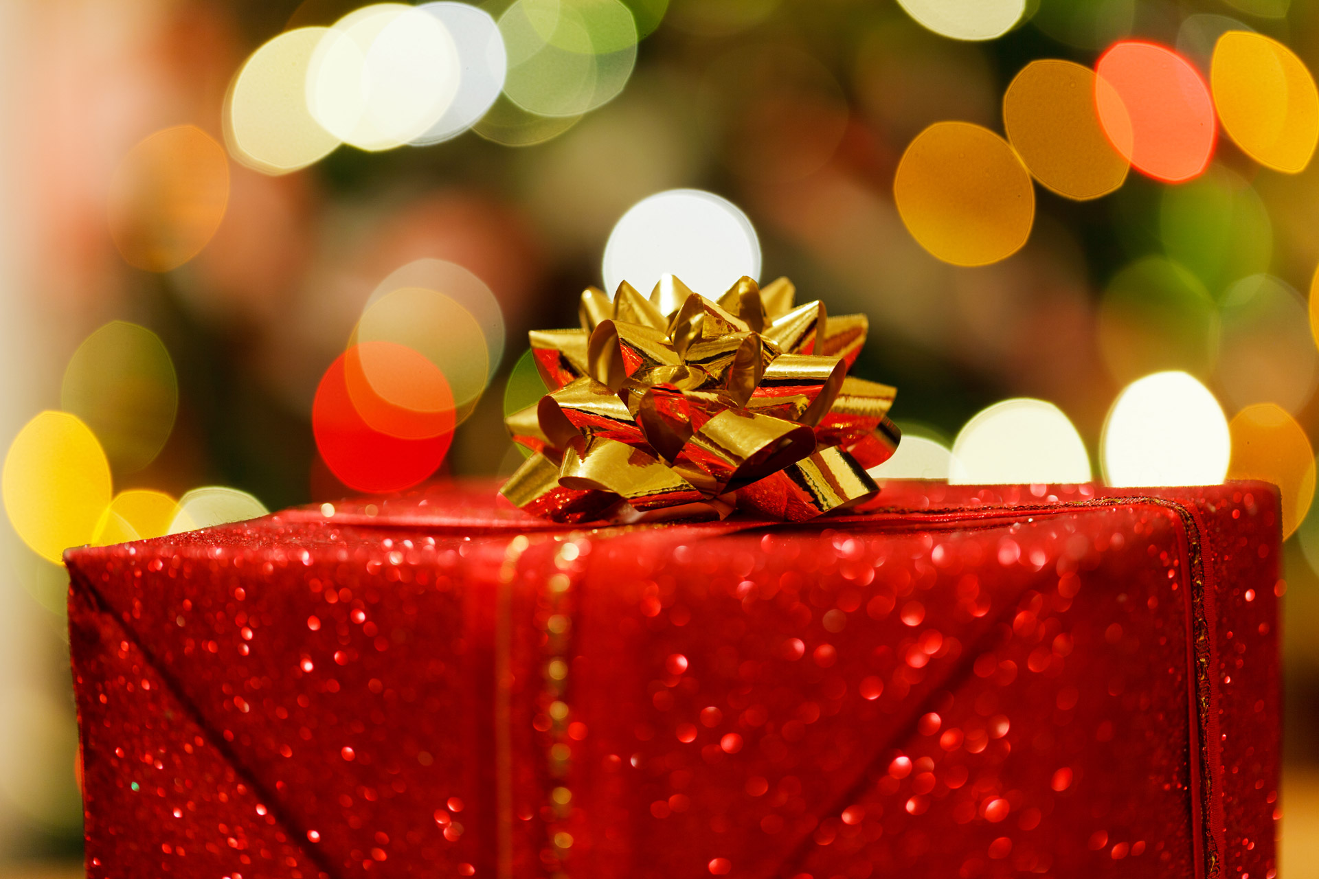 Box wrapped in glittery red wrapping paper with a golden bow and Christmas lights twinkling behind it