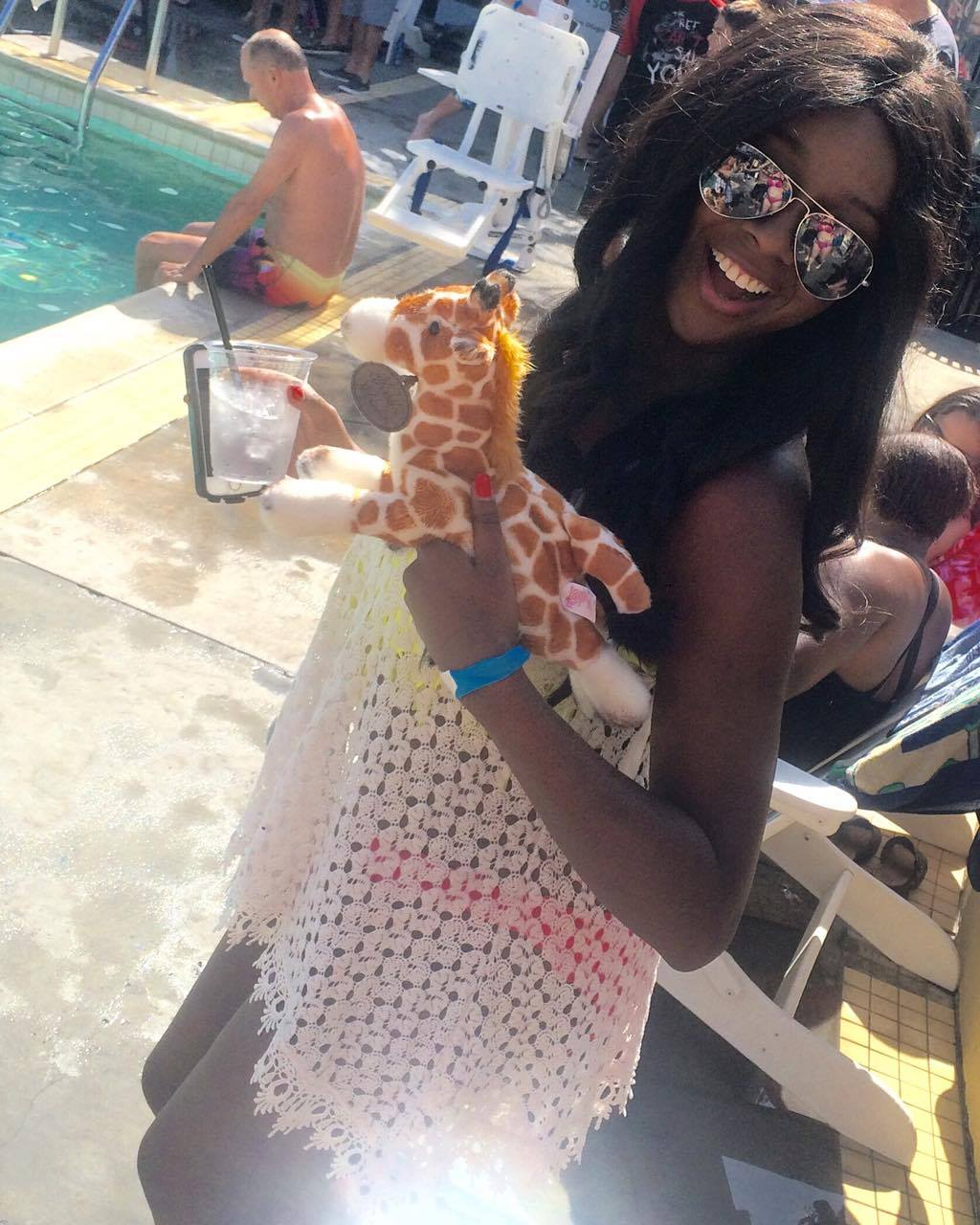 African American woman smiling poolside, wearing a white wrap, holding a glass of ice water, and a stuffed giraffe toy