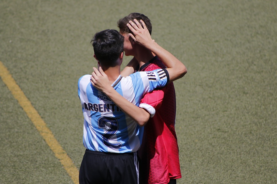 two soccer plays hugging