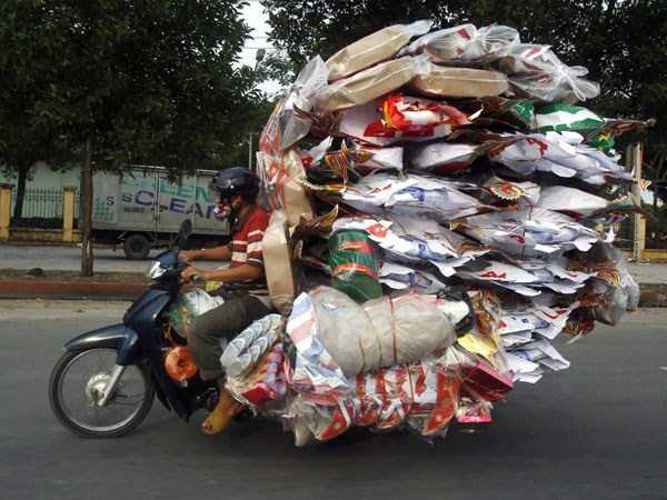 Motorcycle overloaded with plastic bags and unknown items