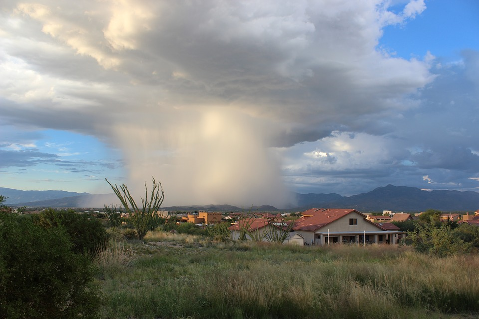 a storm cloud and falling rain onto a small desert town