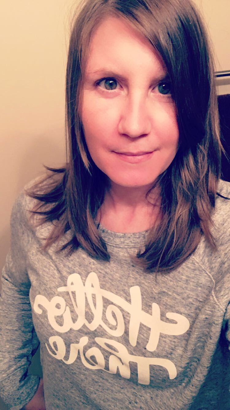 "Smiling woman with brunette hair and brown eyes wearing shirt that reads ""Hello there."""