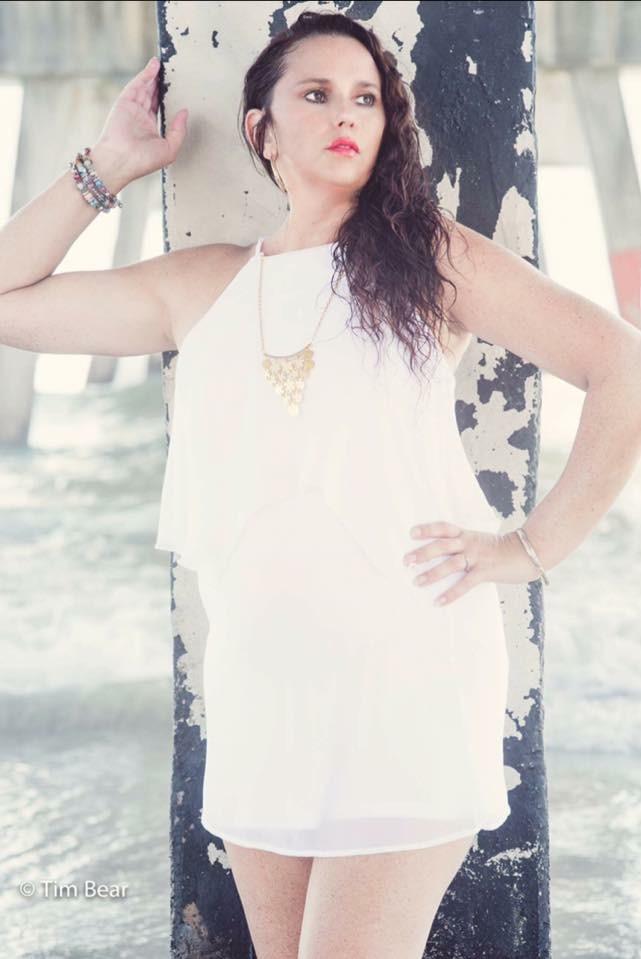 Woman standing against an ocean pier wearing a white dress