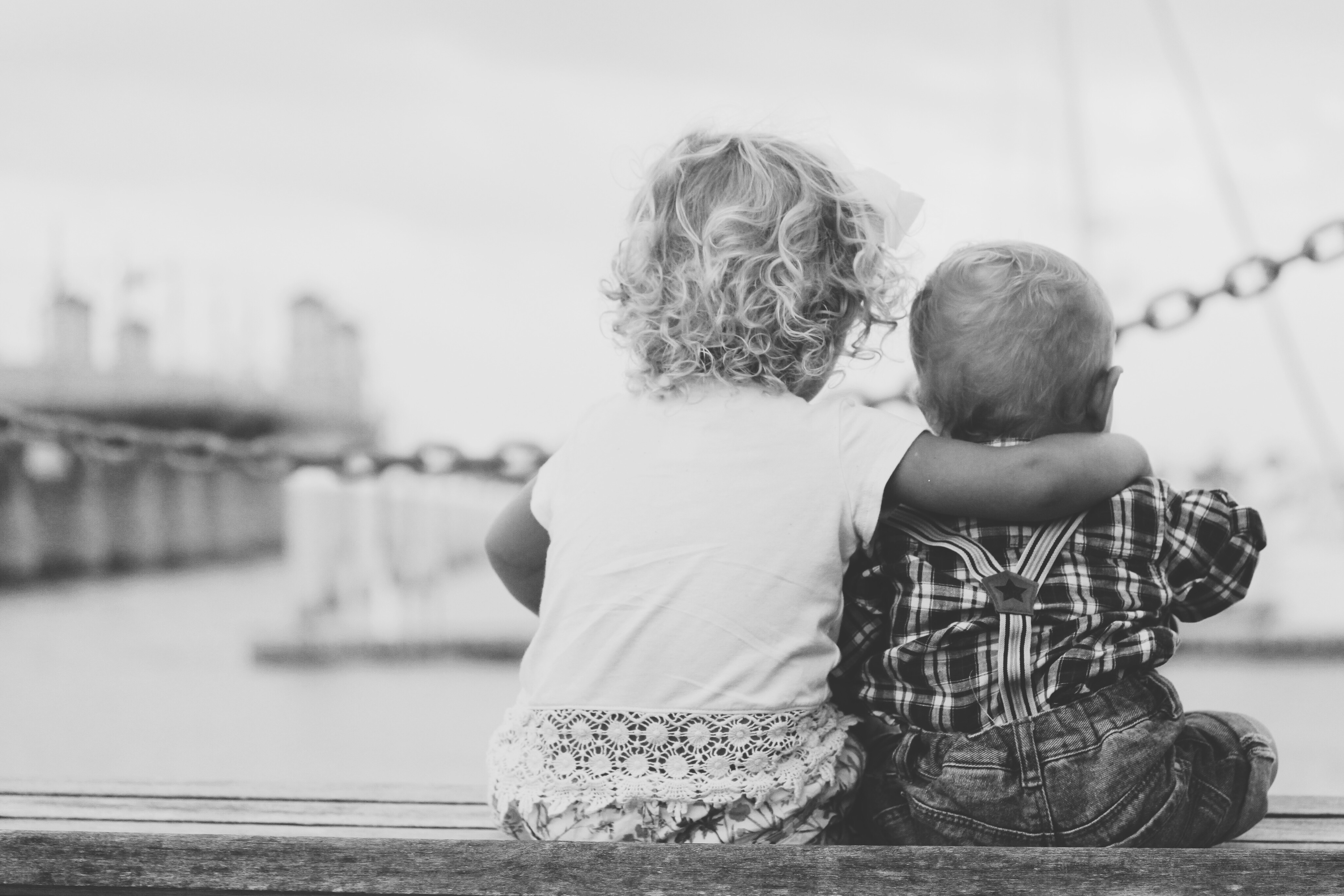 Two toddlers sitting next to each other overlooking an ocean pier