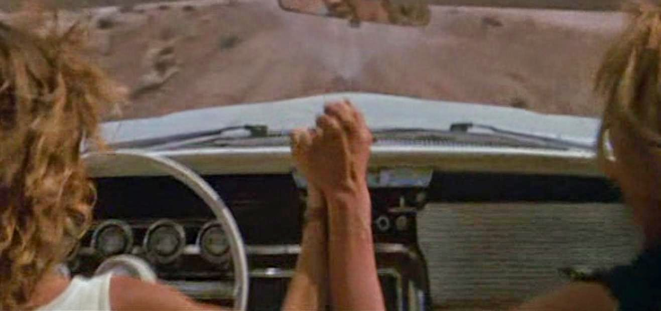 Still shot of Thelma and Louise holding hands as their car goes over a cliff
