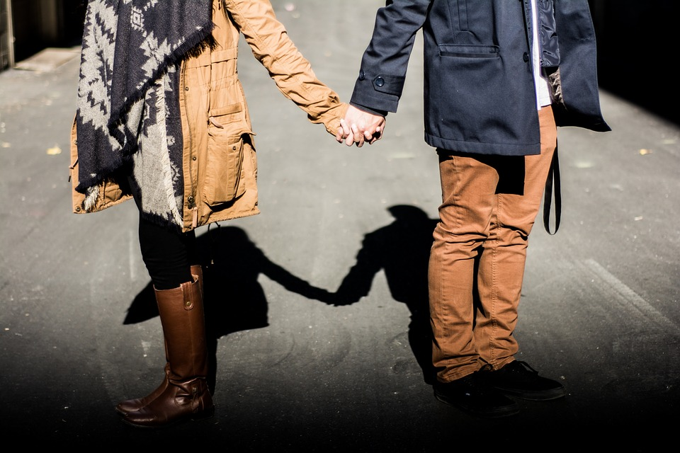Two people holding hands while walking down a street