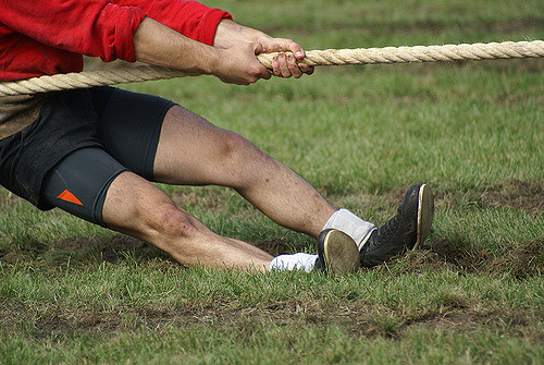 men playing tug of war with a thick rope