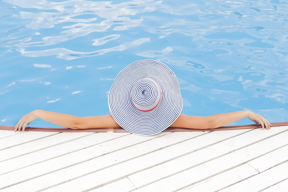 person lounging in a pool wearing a large floppy hat