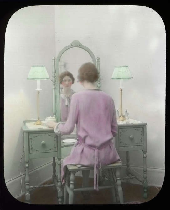 Vintage photograph of woman wearing pink bathrobe and sitting in front of a vanity mirror
