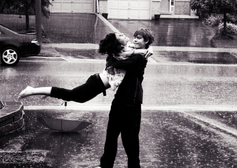 Boy and girl hugging in the rain
