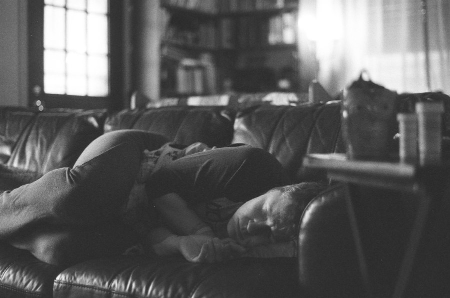 Black and white photograph of me on the couch curled up into a ball with cramps