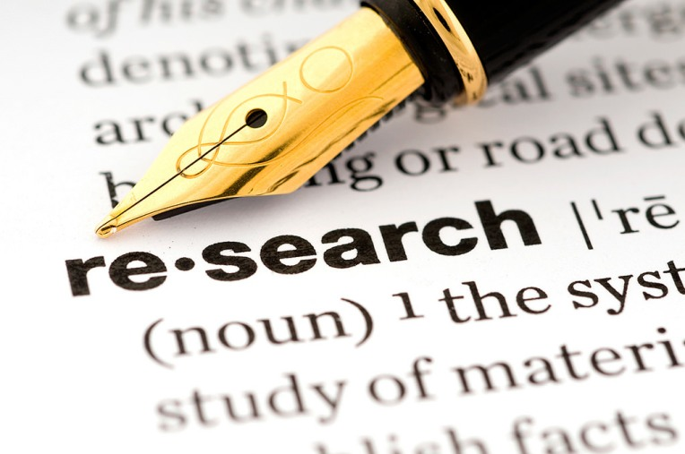 A fountain pen resting on a page containing the definition of research