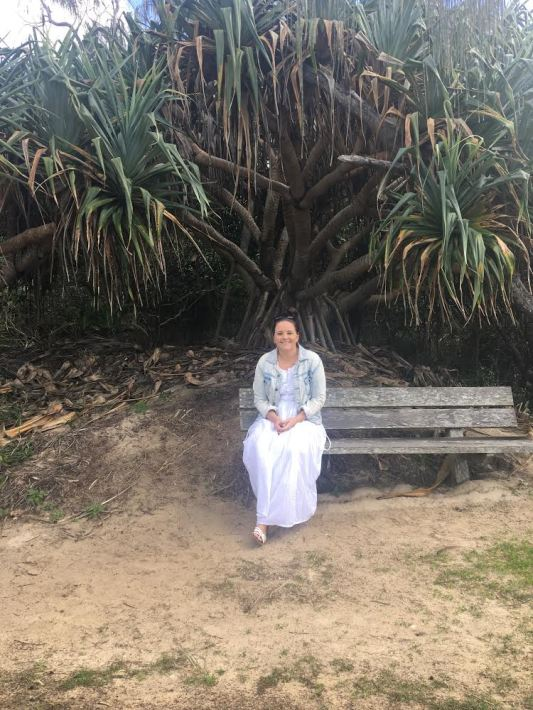 Photo of Coby-Lea sitting on a bench in front of a tree