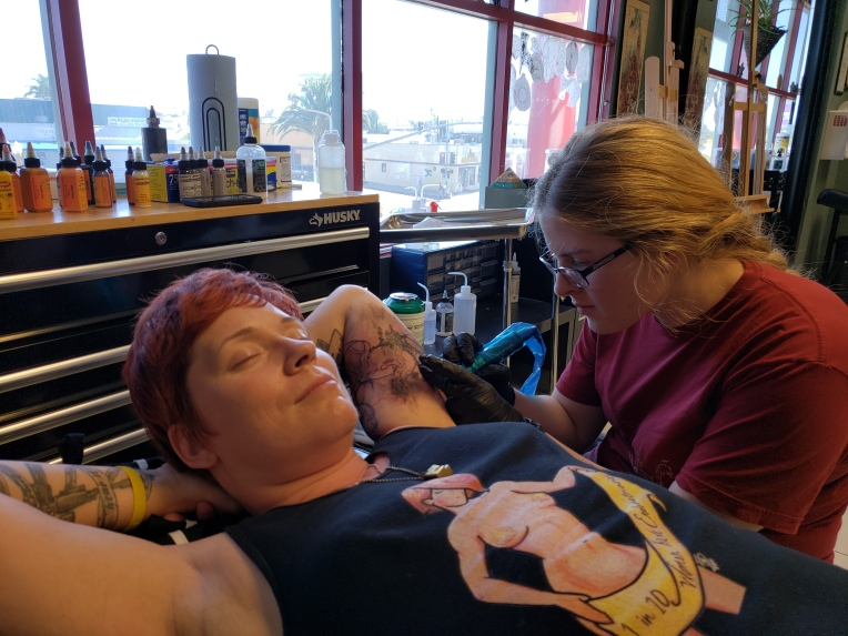Me receiving tattoo on upper backside of left arm near armpit