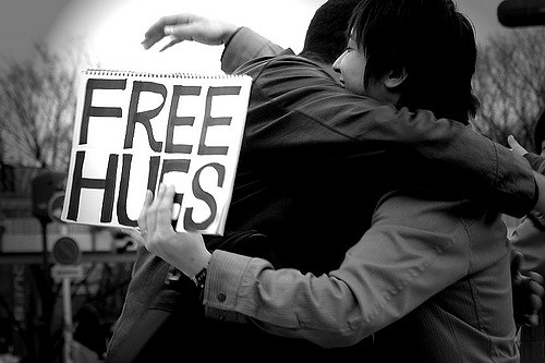 Two people hugging, one is holding a Free Hugs sign