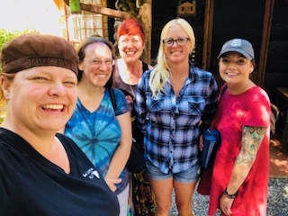 Group photo of 5 women in front of a cabin