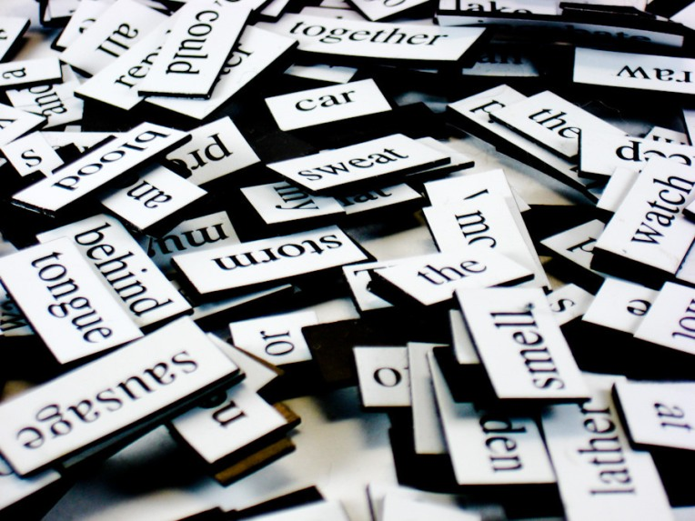 A pile of fridge poetry magnets with various words