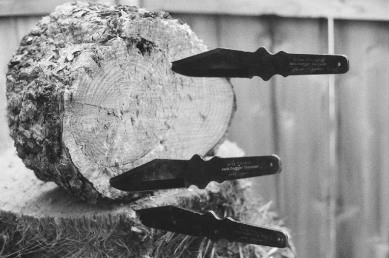 Jack Dagger throwing knives sticking out of a pine round