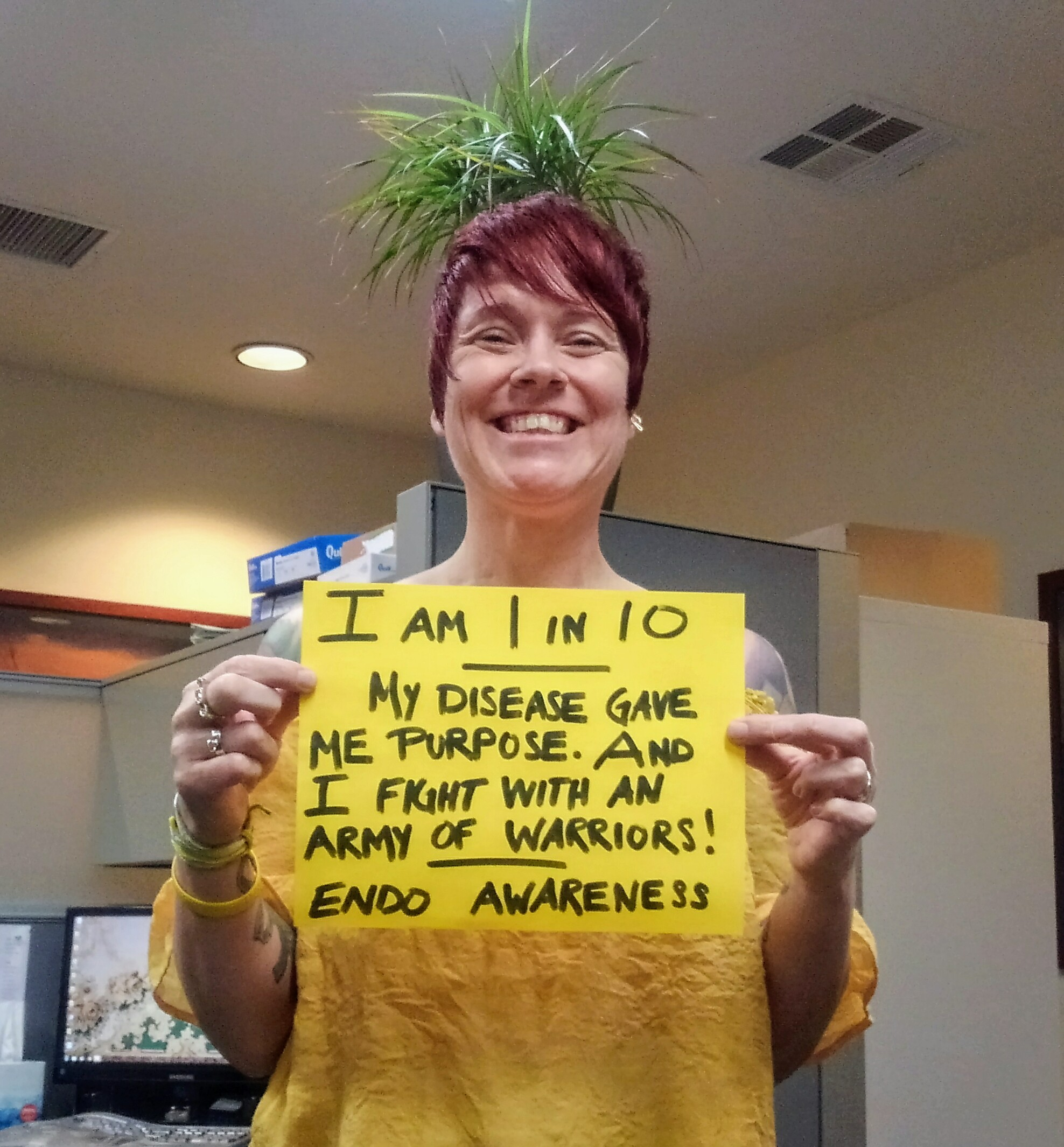 "Lisa Howard holding a sign that reads ""I am 1 in 10. My disease gave me purpose. And I fight with an Army of Warriors.  Endo Awareness"""