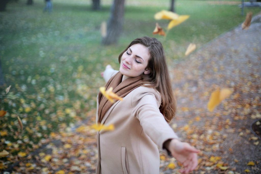 Woman with eyes closed, smiling, and spinning in the falling leaves