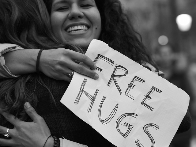 A woman handing out free hugs