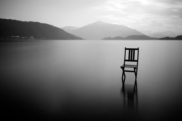 Folding chair atop a quiet lake in the mountains