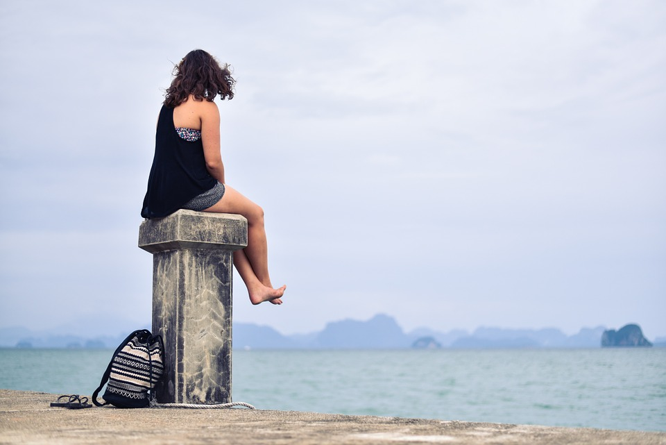 Woman sitting on pedestal looking out at the ocean