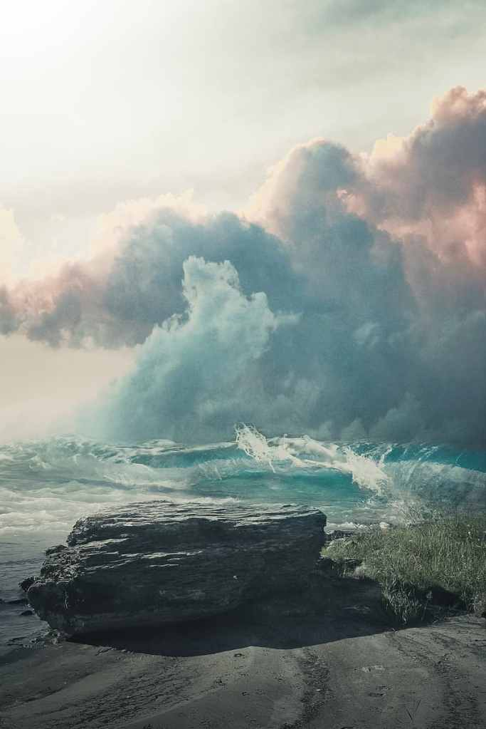 Ocean waves crashing on rocky shore under white clouds