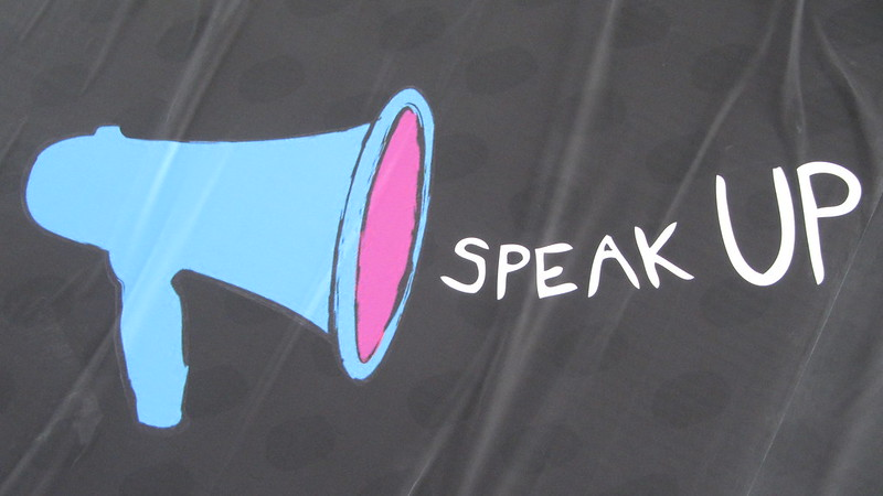 "Banner with megaphone and words ""Speak Up"" next to ti"