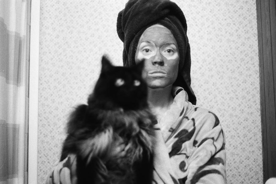 Black and white photo of a woman in bathrobe, wearing a towel on her head, clay mask on her face, holding a cat in the bathroom